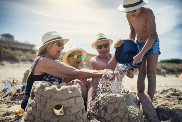 Grandparents with three grandsons happily building a sandcastle on the beach on a beautiful day.